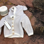 Appalachian Baby baby bear cardigan on beach steps by Fig Tree Yarns