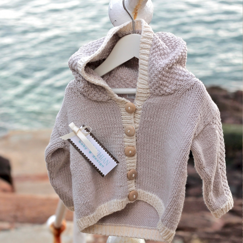 Appalachian Baby baby bear cardigan on beach rail by Fig Tree Yarns